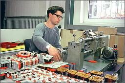 Un opérateur fabricant une bobine Mundorf sur une machine de production